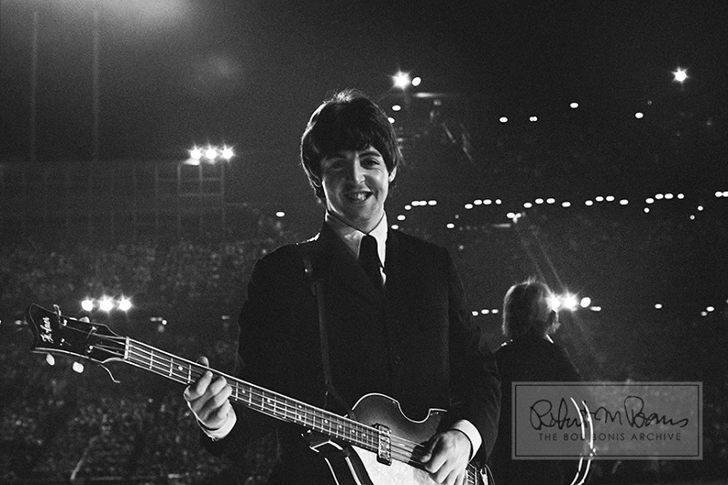 In a beautifully intimate moment in the middle of 25,000 fans, Paul McCartney turns away from the audience and beams when he finds Bob Bonis. The Bloomington, Minnesota, show on August 21, 1965, was The Beatles' only stop in the Land of 10,000 Lakes on all three US tours. (Image title: Paul McCartney and George Harrison, Metropolitan Stadium, Bloomington, MN, August 21, 1965 #3)