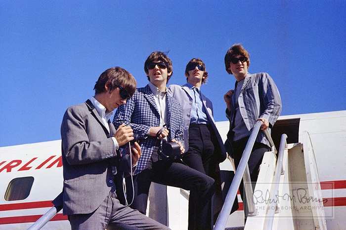 All four Beatles, Paul McCartney, Ringo Starr, John Lennon and George Harrison board an airplane at the SeaTac airport in Washington, Augst 22, 2964