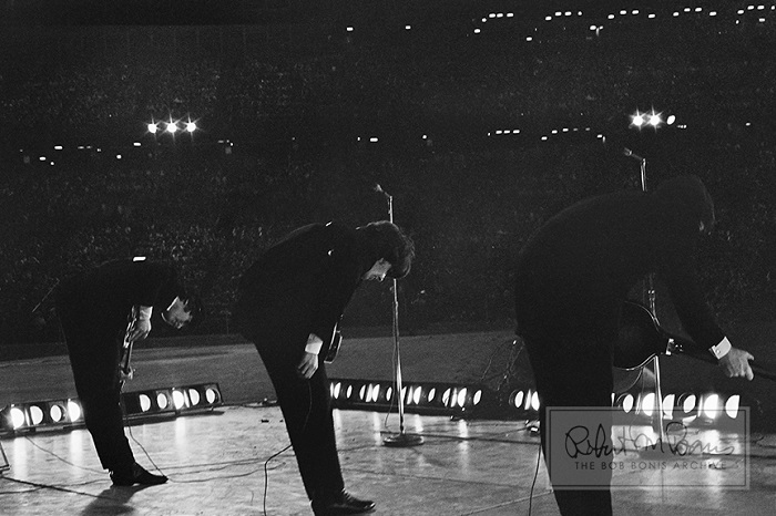 The Beatles take a bow on stage at the Metropolitan Stadium in Bloomington, Minnesota on August 21, 1965. Photo by Bob Bonis